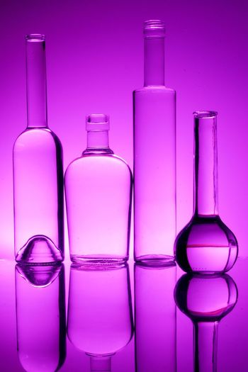 Various Shaped Glass Bottles On Pink Background