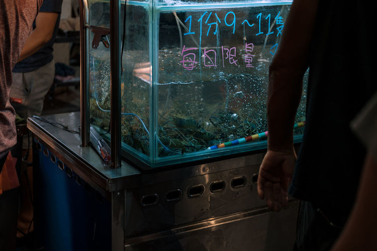 Midsection of people standing by fish tank