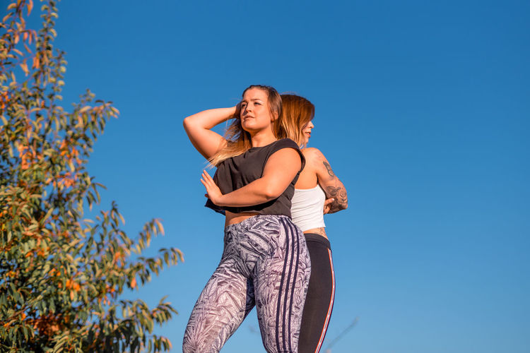 Low Angle View Of Women In Sports Clothing Against Clear Sky