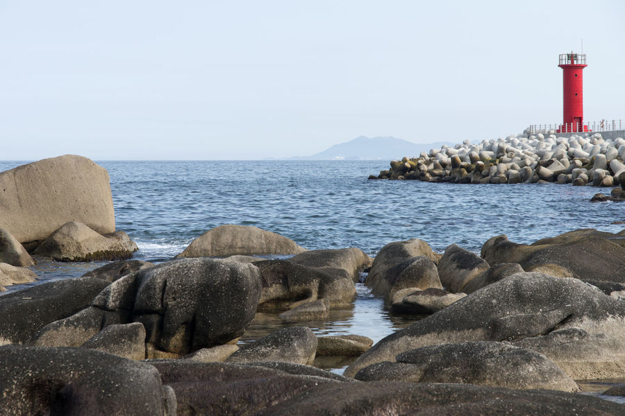 rocky seaside near Jumunjin Port in Gangreung, Gangwondo, South Korea Animal Themes Beauty In Nature Clear Sky Day Horizon Over Water Lighthouse Nature No People Outdoors Rock - Object Scenics Sea Seaside Sky Tranquility Water