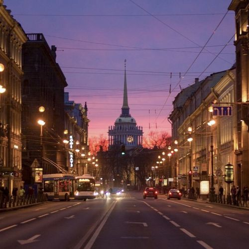 View of city street and buildings at dusk