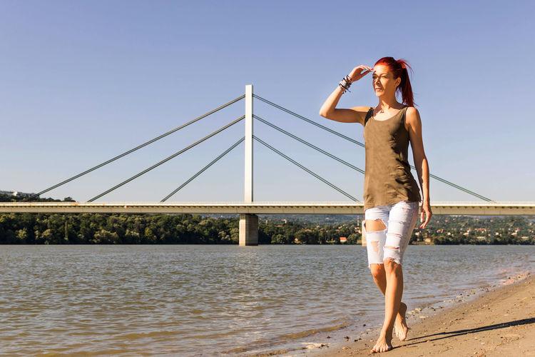 Full length of woman standing on bridge over sea against sky