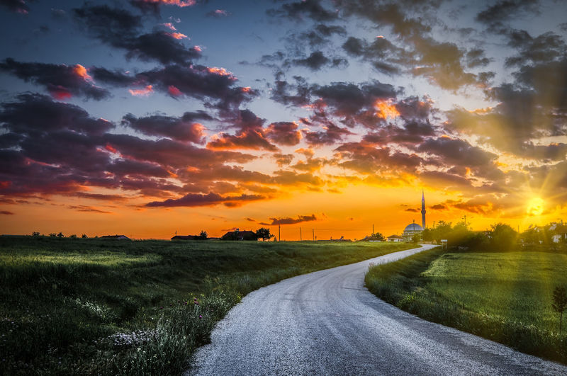 Road to a small village. Sunset Sky Road Cloud - Sky Direction The Way Forward Orange Color Beauty In Nature Transportation Scenics - Nature Nature Field Landscape Environment Land Tranquil Scene Tranquility Diminishing Perspective Plant No People Sun Outdoors