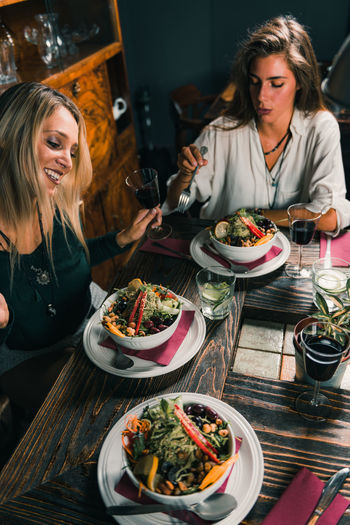 Cheerful Female Friends Eating Food At Table In Restaurant