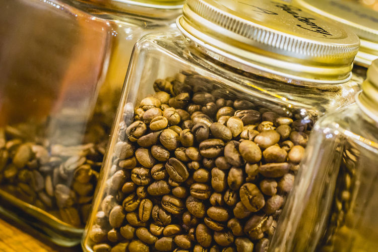 Close-up of roasted coffee beans in mason jar at table