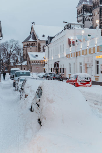 Snow covered road by buildings in city
