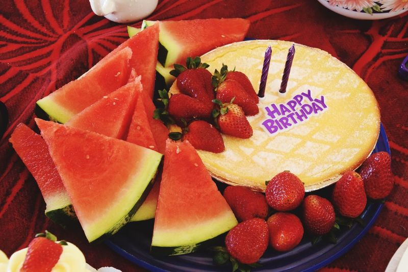 Close-Up Of Birthday Cake With Watermelon And Strawberries On Table