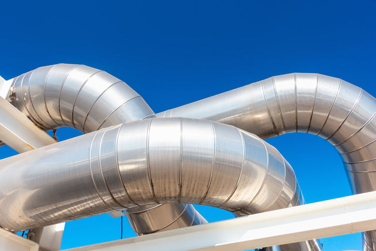 Low angle view of silver pipeline against clear blue sky