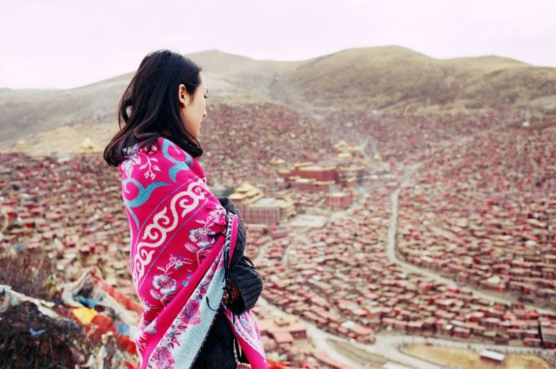 Young woman overlooking townscape against mountains