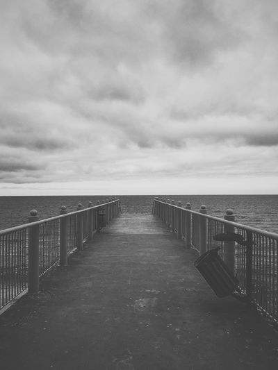 View of pier leading to calm sea