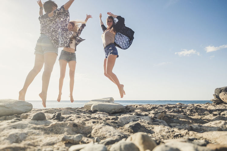 Happy Friends Jumping At Beach Against Sky