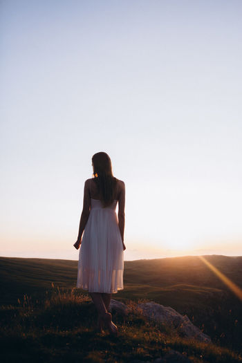 Rear view of young woman standing at field against clear sky
