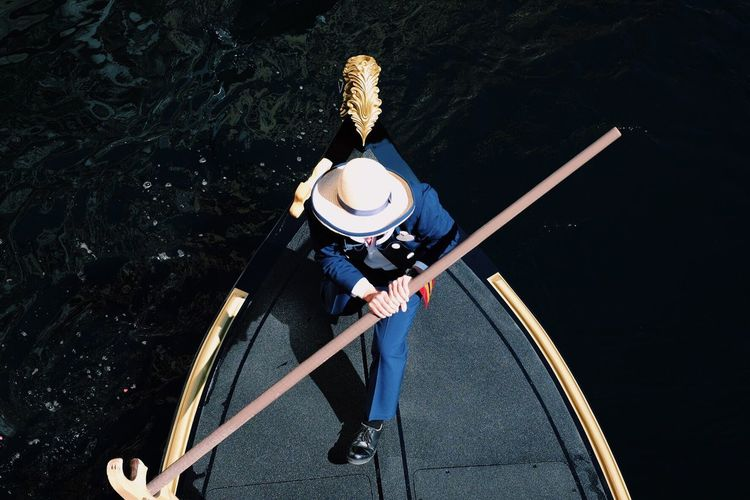 High angle view of man holding oar on boat in river