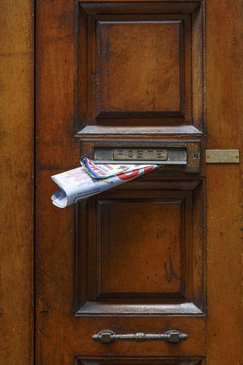 Close-up of mailbox on closed door