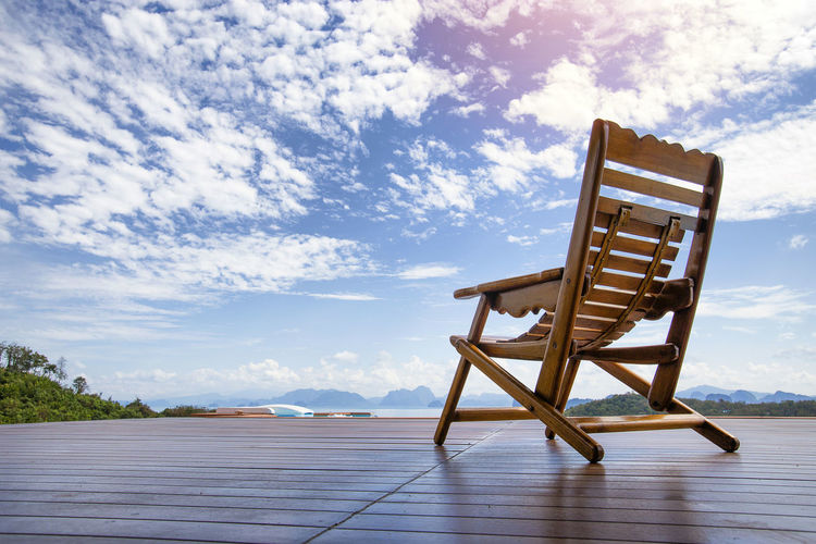 Empty chair on shore against sky