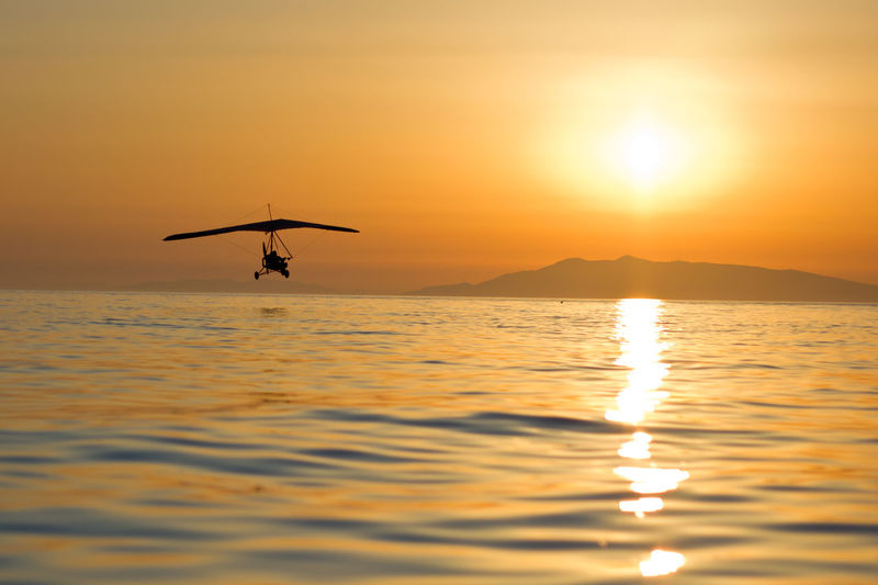 Silhouette hang glider over sea against clear sky during sunset