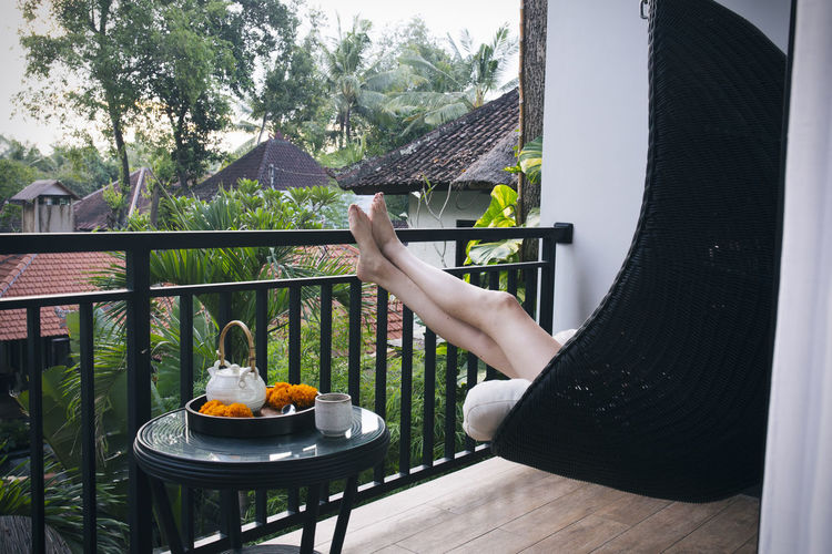 Low section of woman relaxing on swing at balcony