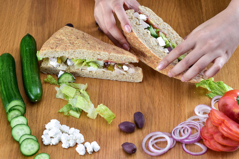 High Angle View Of Woman Preparing Sandwiches On Table