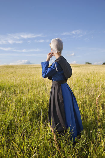 Amish woman in blue dress and black cape in a field Afternoon Amish Amish Country Apron Black Blonde Blue Bonnet Cape  Dress Field Girl Grass Pensive Religion Religious Beliefs Serious Sky And Clouds Standing Sunlight Sunlight ☀ Woman