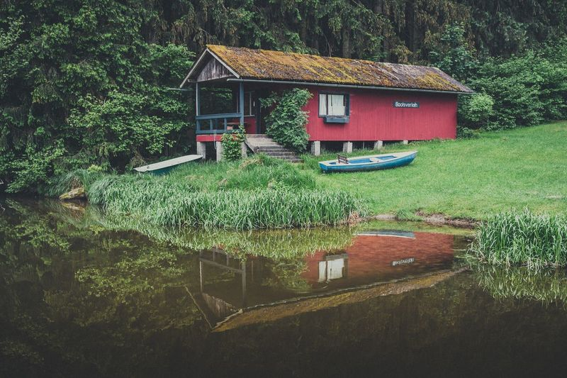 Boat lake hut Plant Built Structure Architecture Building Exterior Tree Green Color Nature High Angle View Land Grass Water House Outdoors No People Hedge Field Day Park Building Growth