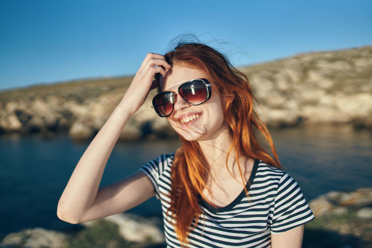 Portrait of smiling young woman wearing sunglasses against sea