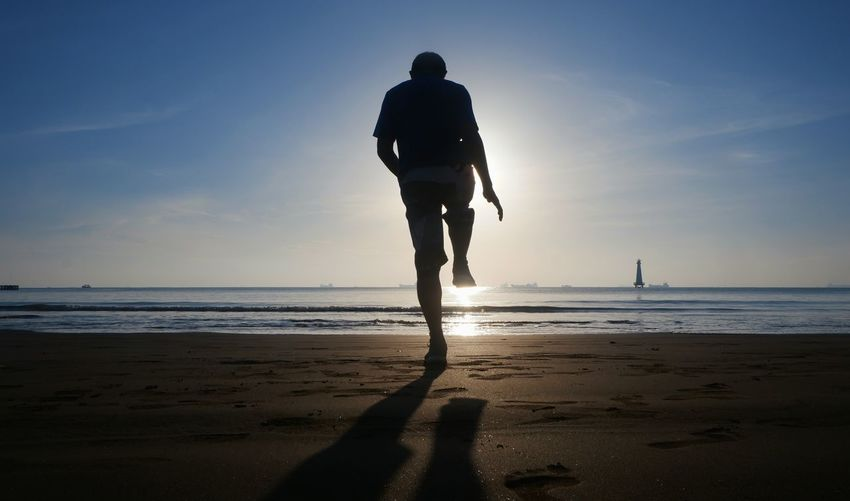 Rear view of silhouette man standing on one leg at beach