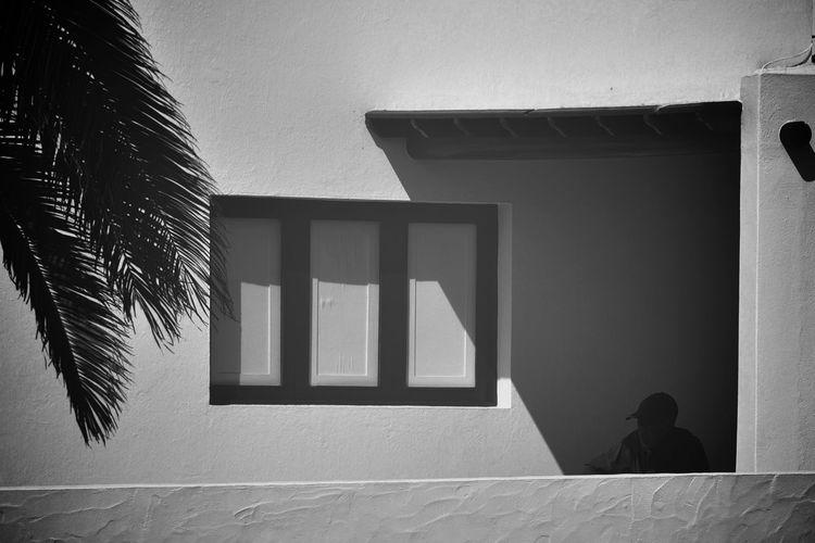 Rear view of man walking through window