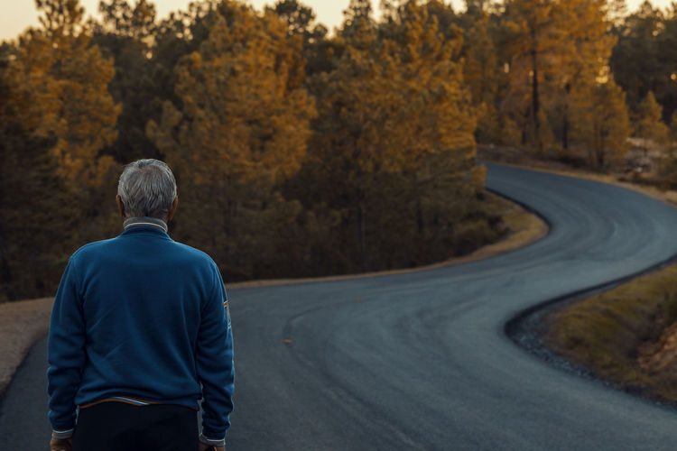 Rear view of senior man standing on road during autumn