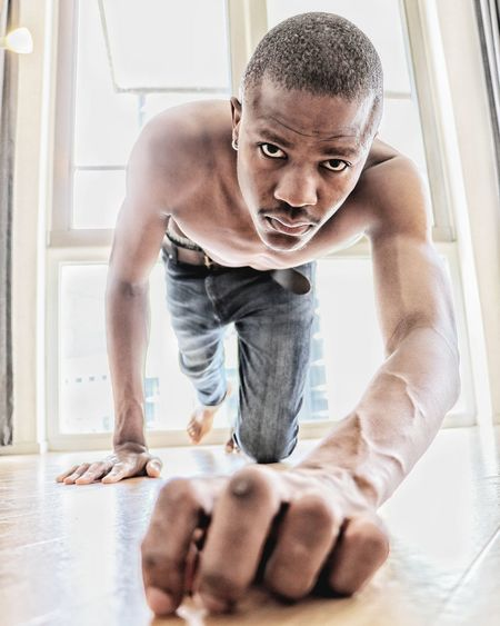 Portrait of shirtless man crawling on floor at home