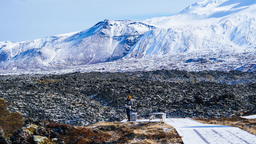 Woman standing on land against snowcapped mountain