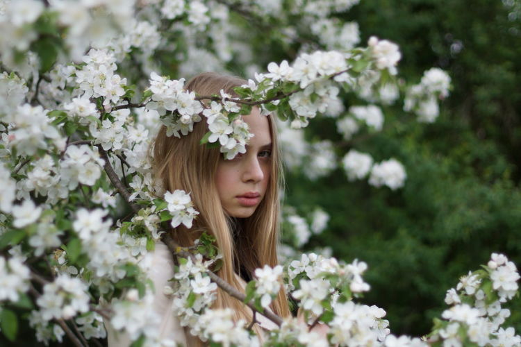 Portrait of young woman with flowers in bloom