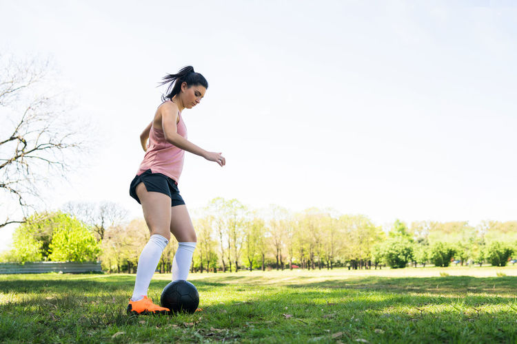 Full length of woman playing with football on field against sky