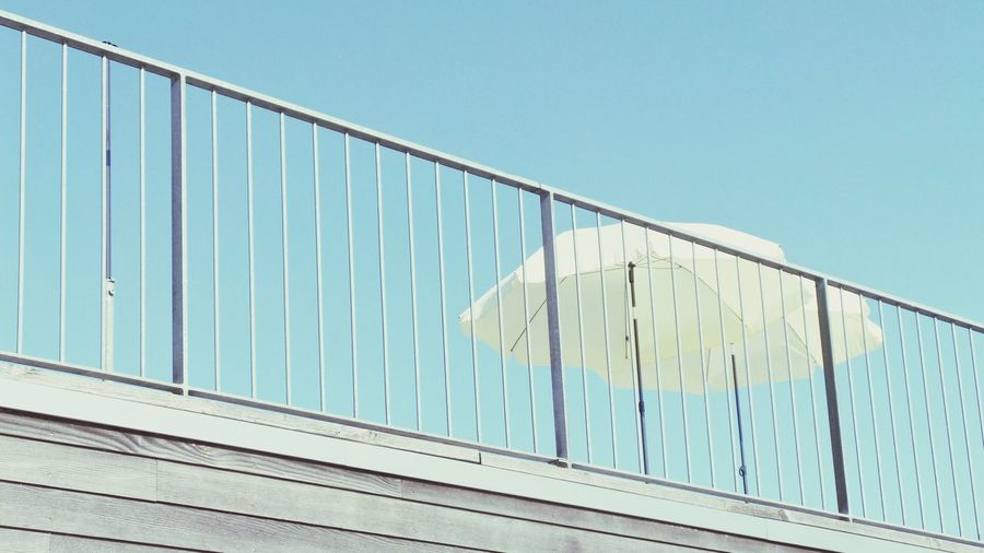Low angle view of umbrella next to railing against clear sky