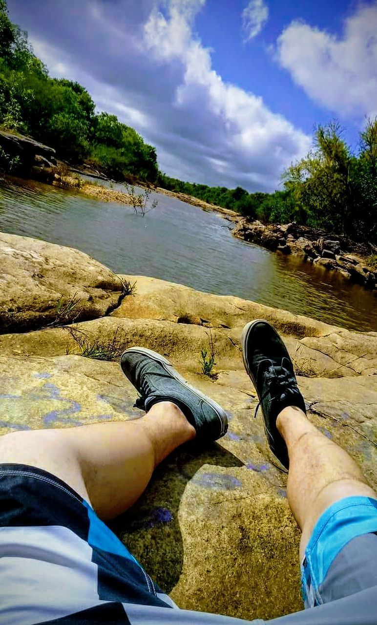 human leg, water, low section, real people, body part, leisure activity, personal perspective, cloud - sky, human body part, sky, lifestyles, nature, men, day, relaxation, one person, shoe, land, plant, outdoors