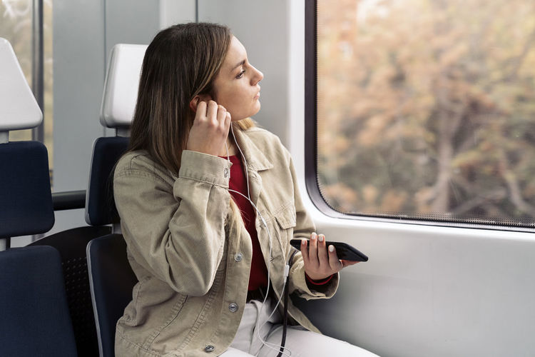 Rear view of woman looking through train window