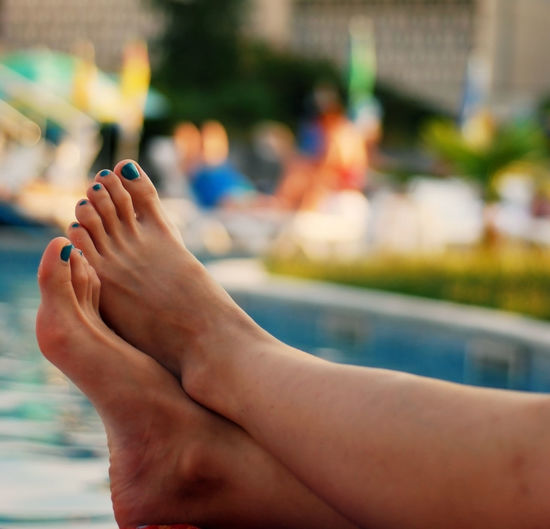 Woman feet with nail polish relaxing by a swimming pool - holiday time. Barefoot Close-up Colorful Feet Female Holiday Human Body Part Human Leg Leg Leisure Leisure Activity Lifestyles Nail Polish Pool Poolside Relaxation Relaxation Time Resort Summer Summertime Swimingpool Vacations Water Weekend Women