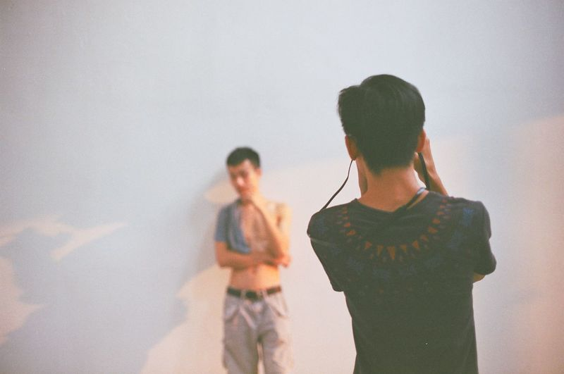 Rear view of man photographing friend standing against wall