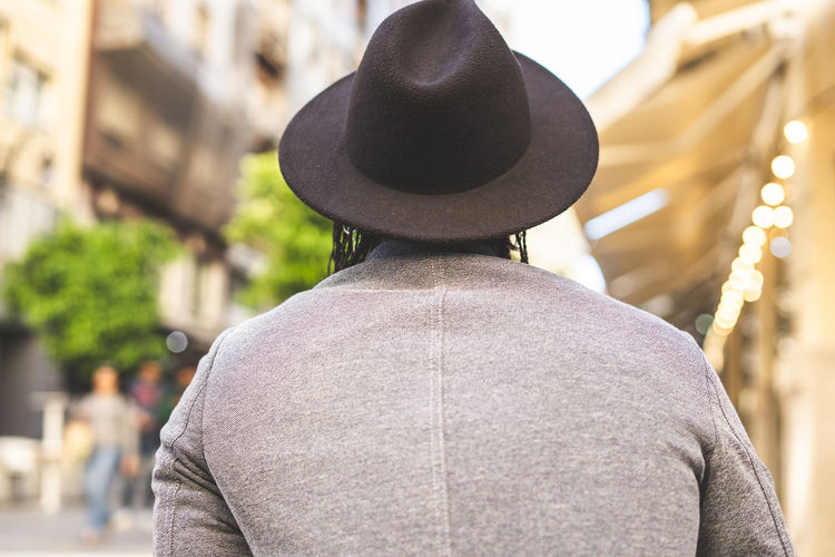 Rear view of man wearing hat standing against city