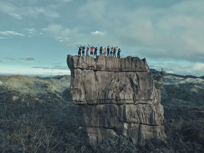 Friends Posing While Standing On Cliff Against Sky