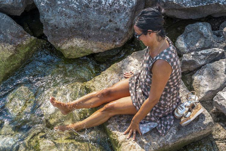 High angle view of woman sitting on rock at beach