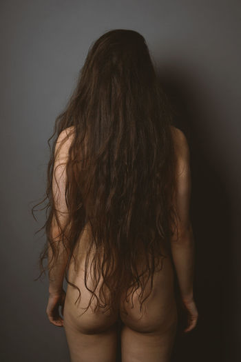 Rear view of naked woman standing against gray background