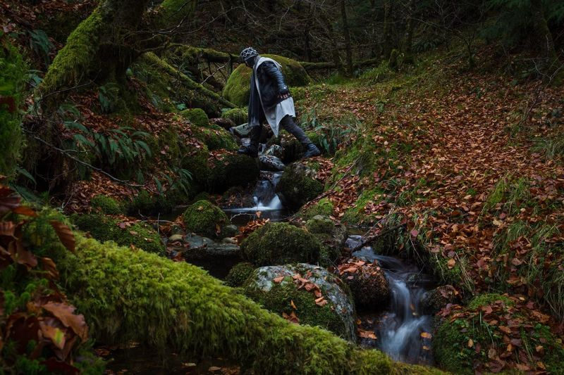 Man walking over stream in forest during autumn