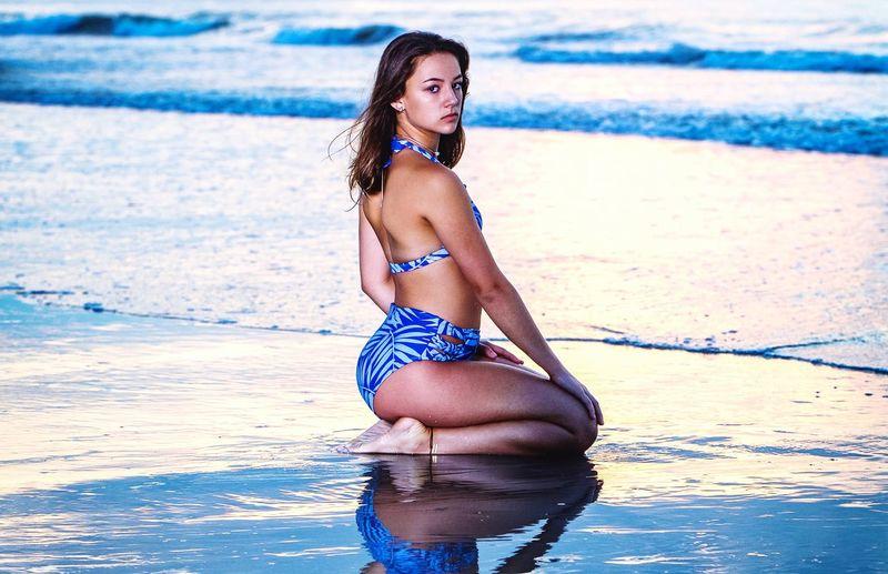 Teenage girl in bikini kneeling on shore at beach