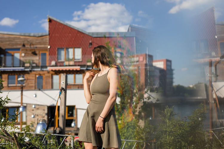 Young woman standing by building against sky