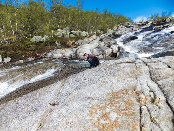 Low Angle View Of Woman Drinking Water From Stream Flowing Through Rocky Hill