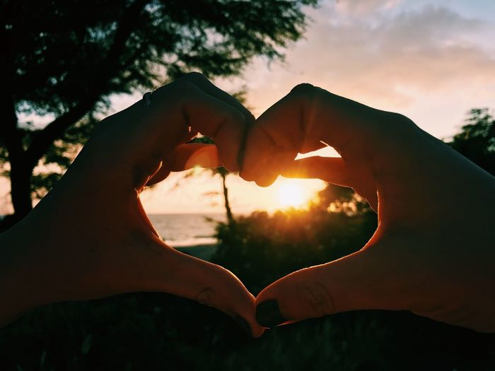 Cropped hands of woman making heart shape against sky during sunset