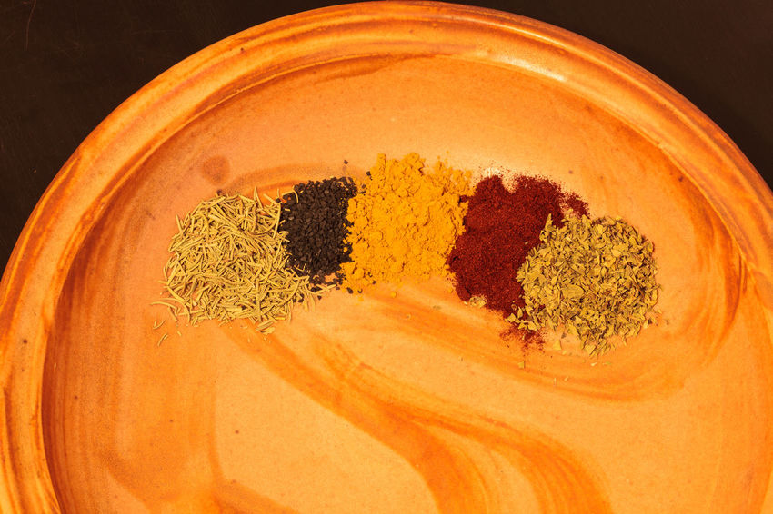 Mix of red cayenne pepper, yellow turmeric, green rosemary and oregano herbs with black sea salt on an earthy pottery plate. Black Sea Salt Cayenne Pepper Close-up Herbs No People Oregano Pottery Red Pepper Sea Salt Spice Spices Tumeric Yellow