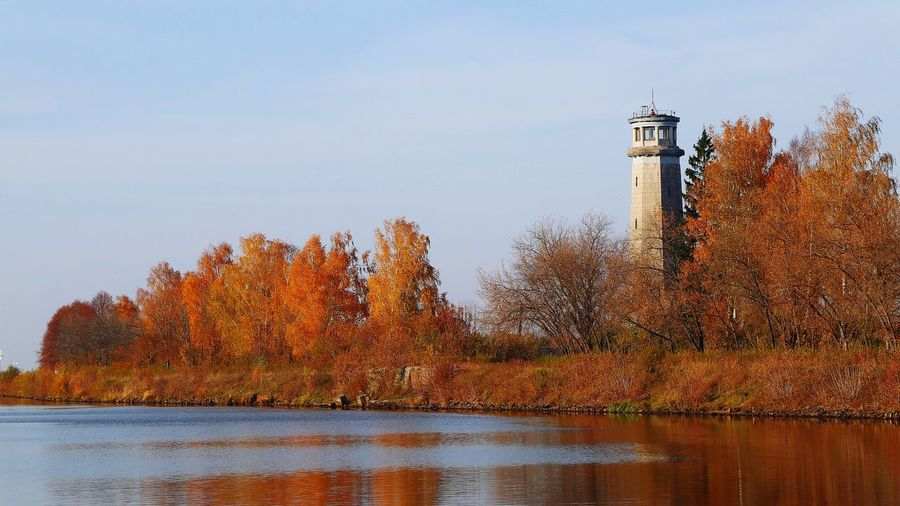 Lighthouse by lake against sky during autumn
