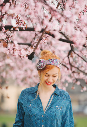 Portrait of smiling young woman with pink cherry blossom on tree