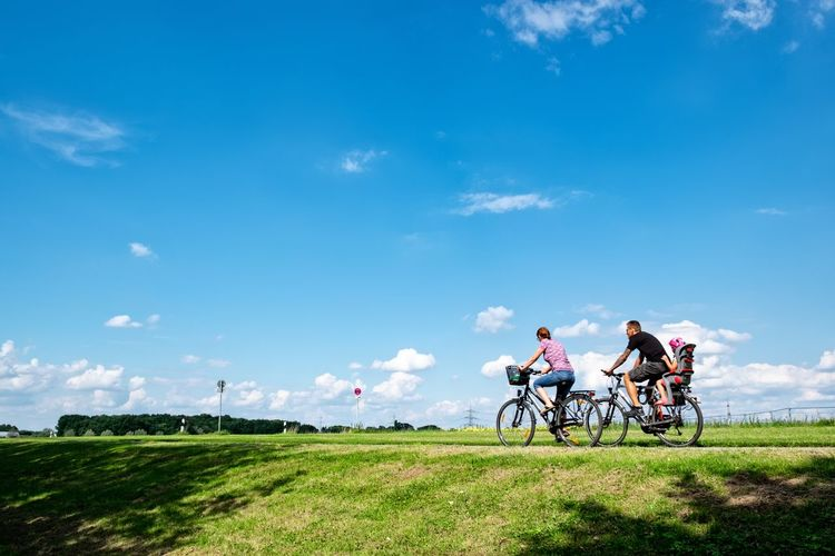 Family Riding Bicycles On Grassy Field Against Blue Sky